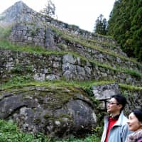 A couple visit the Iwamura Castle ruins in Ena, Gifu Prefecture, that are recently attracting tourists amid growing popularity of stone castle walls. | CHUNICHI SHIMBUN
