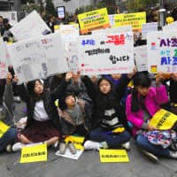 South Korean protesters hold up signs during a demonstration supporting 'comfort women' held in front of the Japanese Embassy in Seoul on Wednesday.   AFP-JIJI