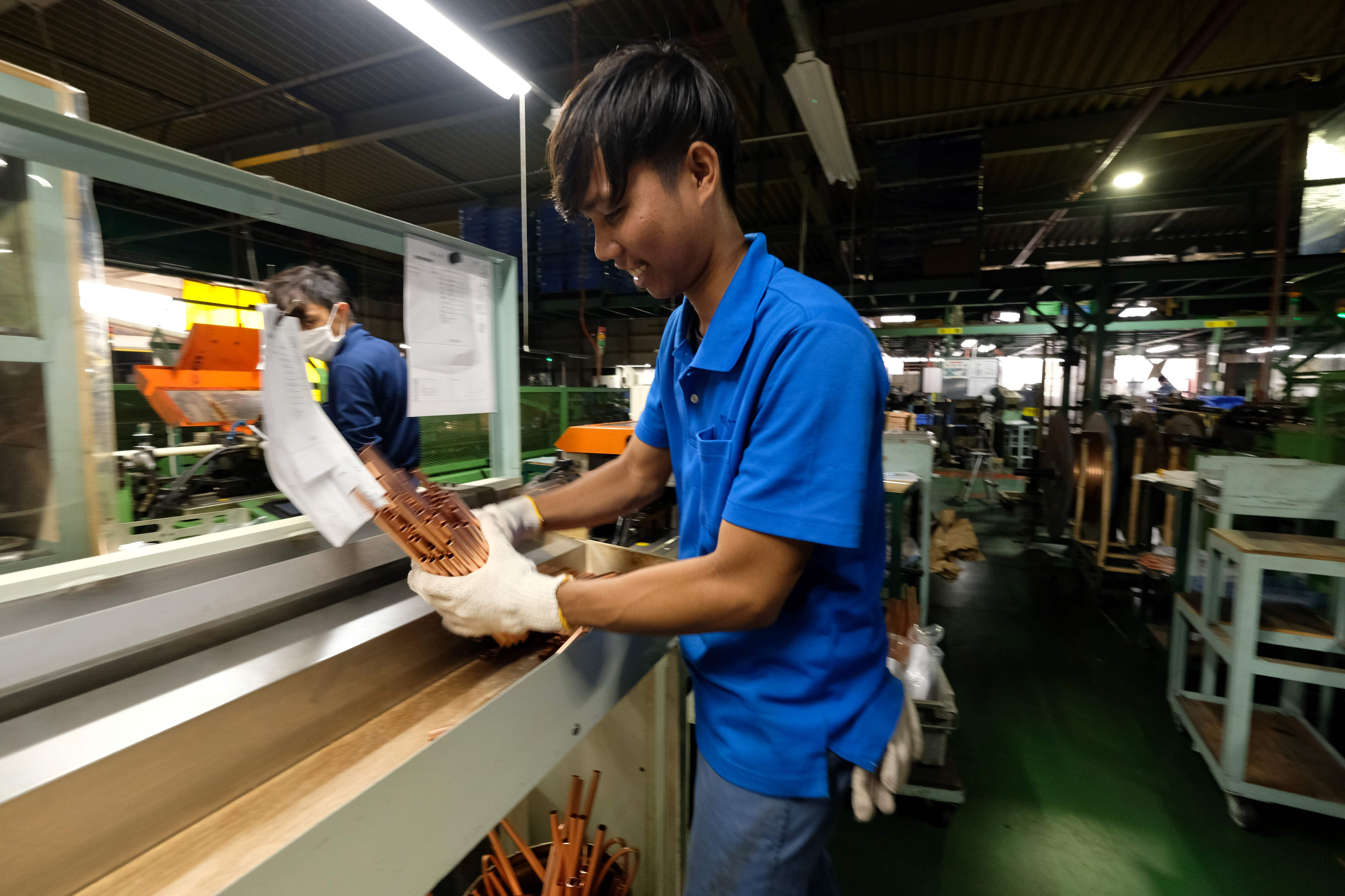 Jaman, an Indonesian worker, processes copper pipes at a factory in Oizumi, Gunma Prefecture, last month.   AFP-JIJI