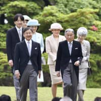 Crown Prince Naruhito (front, left) walks with Emperor Akihito and other members of the Imperial family in Akasaka Imperial Garden in Tokyo in April. | KYODO