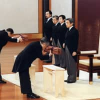 Emperor Akihito (right) attends a ceremony at the Imperial Palace in Tokyo to ascend the Chrysanthemum Throne after his father, Emperor Hirohito, died in January 1989 aged 87. | KYODO