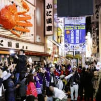 People celebrate in Osaka's Dotonbori area, following the good news that Osaka will host the World Expo again. | KYODO