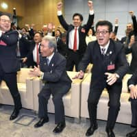 Supporters of Osaka's 2025 Expo bid, including Osaka Prefecture Governor Ichiro Matsui (second from right) and Osaka Mayor Hirofumi Yoshimura (center, second row), celebrate in Paris immediately after the announcement that the city would be hosting the event for the second time.  | KYODO