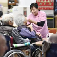 An Indonesian care worker tends to a resident at a facility in Tenri, Nara Prefecture, in May 2017. | KYODO