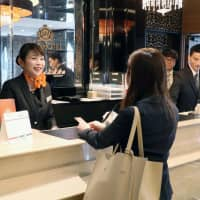 Taiwanese clerk Liang I-ting helps a guest at a hotel near Tokyo's Nippori Station in April 2017. | KYODO
