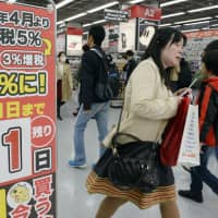 Shoppers are seen at an electronics retail store in Tokyo on March 31, 2014, the day before the consumption tax was raised to 8 percent. | KYODO
