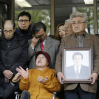 Kim Sung-joo (center), one of the plaintiffs of a case involving wartime laborers, speaks in front of South Korea's Supreme Court in Seoul on Wednesday after it ordered Mitsubishi Heavy Industries Ltd. to pay damages to two groups of South Koreans. | AP