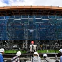 Construction continued Wednesday on Ariake Gymnastics Centre's giant timber roof. It is said to be the largest of its kind in the world.   YOSHIAKI MIURA