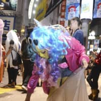 Manami Suzuki, 27, picks up trash on a street in Tokyo's Shibuya Ward early Thursday after the area was swamped with Halloween revelers. | KYODO
