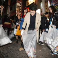Young people pick up trash on a street in Shibuya Ward early Thursday after a busy Halloween night. | KYODO