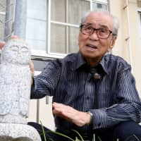Yoshinori Kato, 90, talks about his A-bomb experience while touching the statue of Jizo, the guardian of children, which he donated to Danbara Elementary School. | CHUGOKU SHIMBUN