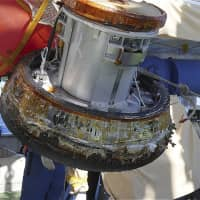A capsule containing samples from the International Space Station is recovered after it splashes down into the Pacific Ocean near Minamitorishima Island, Japan's easternmost territory, on Sunday. | JAXA / VIA KYODO