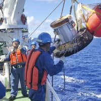 A capsule containing samples from the International Space Station is recovered Sunday after splashing down into the Pacific Ocean near Minamitorishima Island, Japan's easternmost territory. | JAXA / VIA KYODO