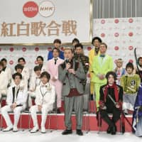 Issa (front row, third from right), lead singer of Da Pump, speaks Wednesday at a news conference held at NHK in Tokyo, where the public broadcaster announced the lineup for its annual New Year's Eve live music program. | KYODO