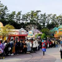 A photo provided by a visitor to Tokyo Disneyland shows people lining up for an attraction featuring Mickey Mouse on Sunday. Faces are blurred for privacy reasons. | KYODO