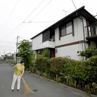 A woman cleans up the road behind her house in the city of Nishi-tokyo, as she started licensed private lodging in June. | KYODO