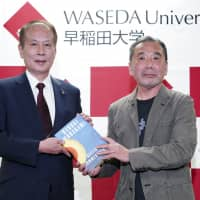 Haruki Murakami (right) poses for photographers with Kaoru Kamata, president of Waseda University, during a news conference in Tokyo on Sunday. | AP