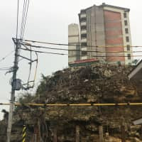 A cliff at the foot of prefectural housing in the Mizugama district of Kadena, Okinawa Prefecture, has a high risk of rockfalls, but the prefectural government cannot proceed with repair work because of unclaimed graves carved into it.   THE OKINAWA TIMES