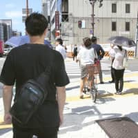 Honed over four decades, Osaka police use facial recognition skills to arrest dozens of wanted criminals every year