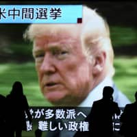 People walk past a huge public TV screen in Tokyo on Wednesday showing a news program covering the U.S. midterm elections. | AP