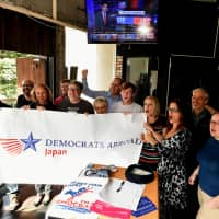 Democrats in Tokyo respond with excitement Wednesday in the capital's Roppongi district as they watch how the U.S. midterm elections are unfolding at home. | YOSHIAKI MIURA