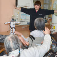 A robot participates in an exercise session for elderly people at a nursing care facility in Tokyo in January. | KYODO