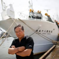 Shigeru Saito, captain of the squid fishing ship Hoseimaru No.58, poses in front of his boat at a port in Sakata, Yamagata Prefecture, on June 5. | REUTERS