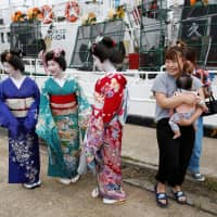 Entertainers wearing kimono attend a ceremony celebrating the departure of the squid fishing ships at a port in Sakata, Yamagata Prefecture, on June 6. | REUTERS
