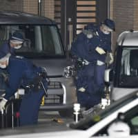 Police examine the area around the house where three people in a family were stabbed to death in Hirakata, Osaka Prefecture, on Thursday. | KYODO