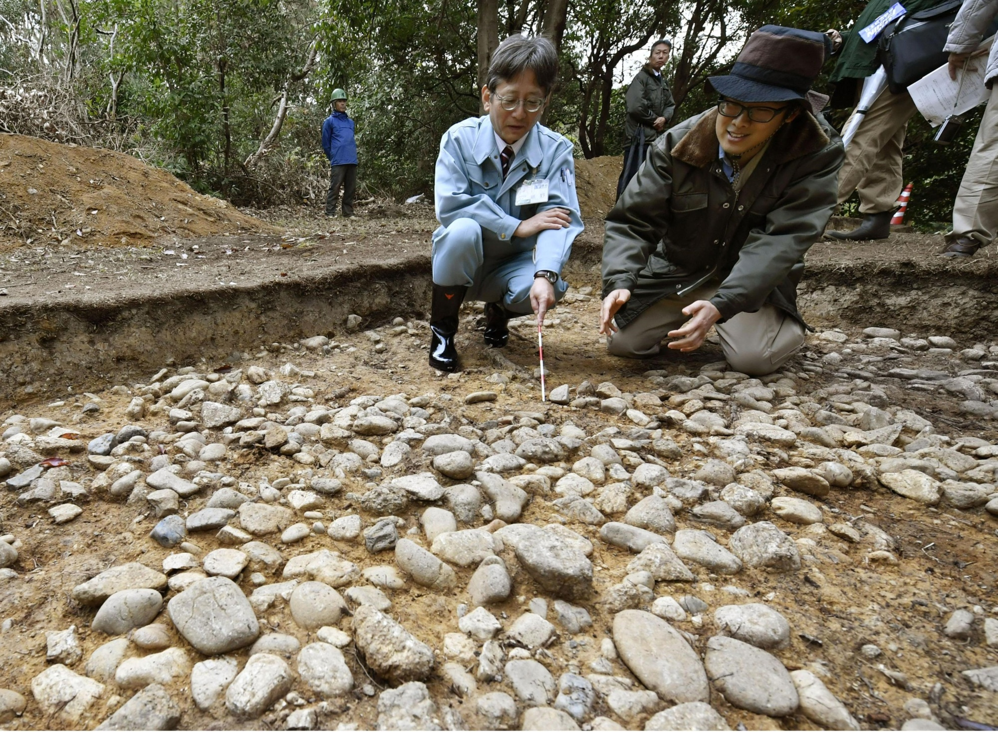 An official (left) from the city of Sakai in Osaka Prefecture and a representative of the Imperial Household Agency explain a stone-paved greenbelt surrounding the Daisen Kofun tomb on Thursday. | KYODO