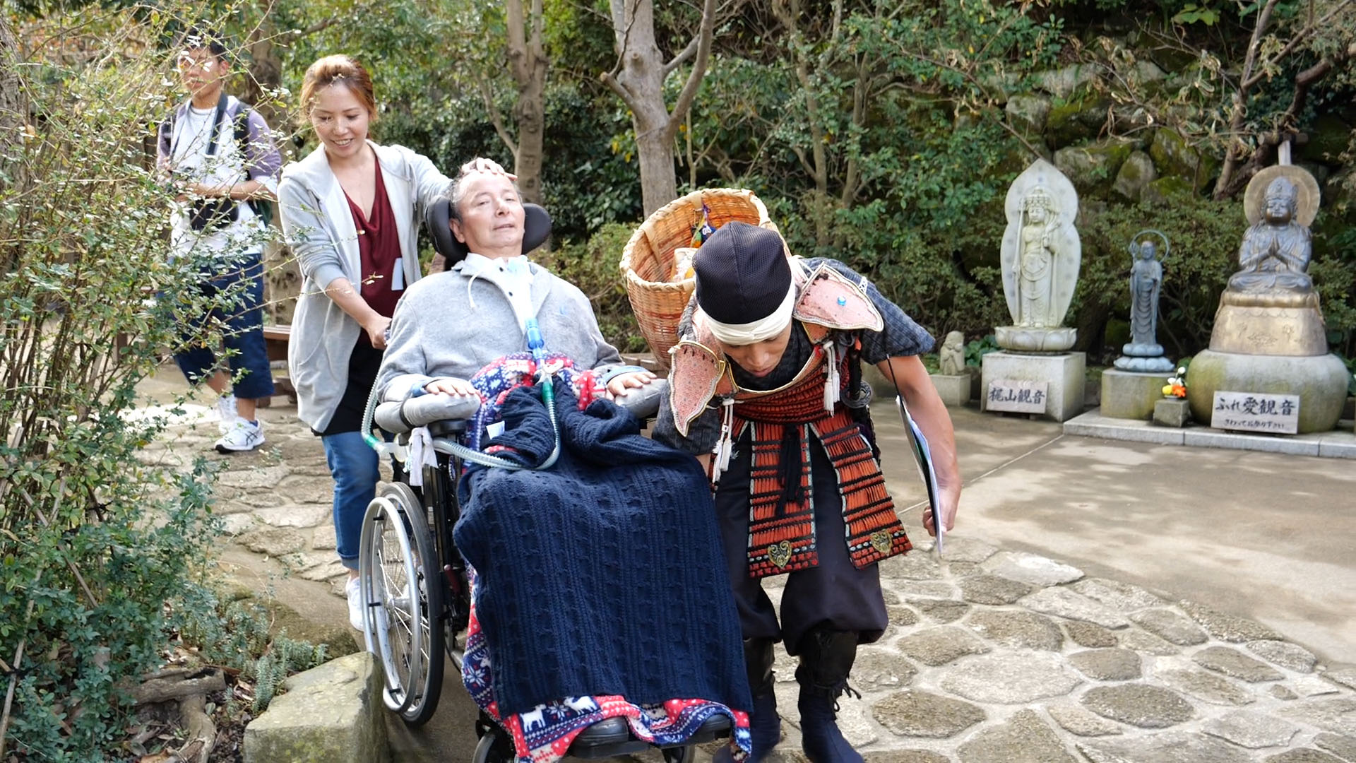 Tomoya Takano (right), the creator of a tour for people with disabilities, helps Hiroshi Matsuyama, who has ALS, navigate a bumpy path at Hase Temple in Kamakura, Kanagawa Prefecture, on Oct. 14.