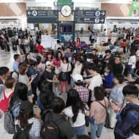 Foreign tourists gather at New Chitose Airport in Sapporo in September. | KYODO