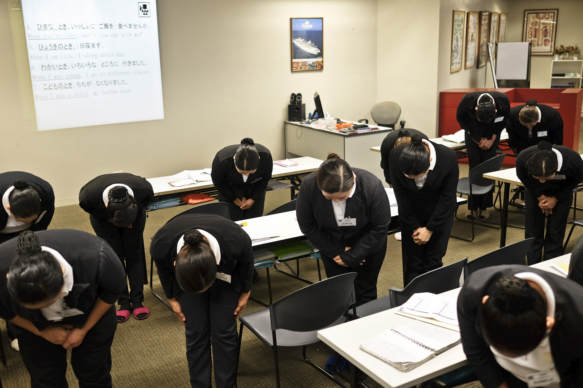 Trainee housekeepers practice bowing in Manila in 2016 in preparation for working in Japan.   BLOOMBERG