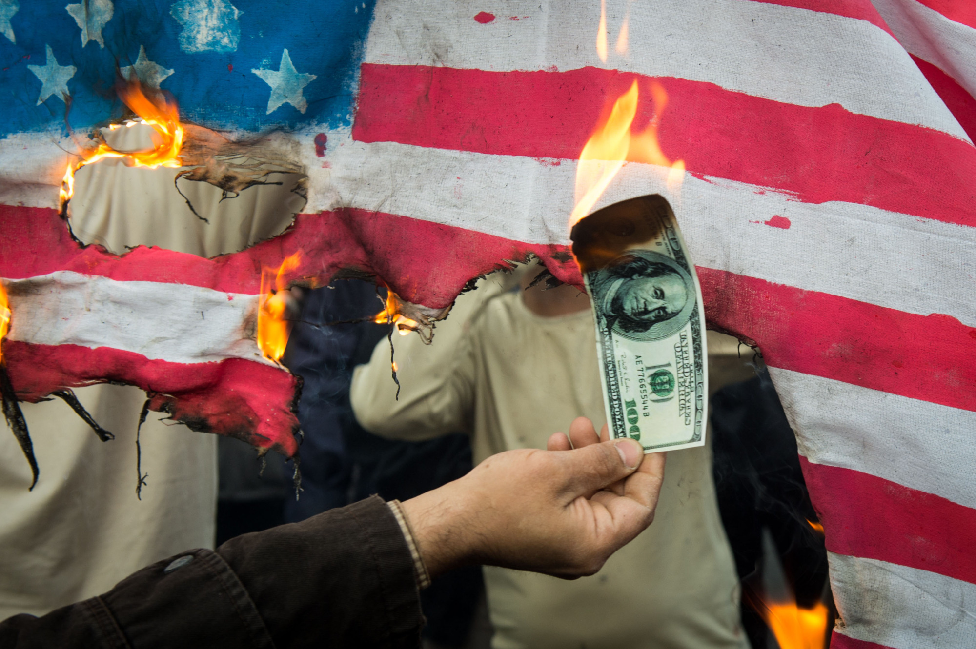 Protesters burn an American flag and money during a demonstration on the anniversary of the U.S. embassy seizure in Tehran on Sunday, the same day that the latest round of U.S. economic sanctions on Iran went into effect. | BLOOMBERG
