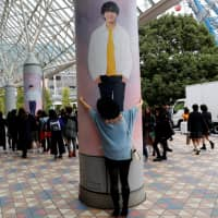 Fan favorite: A woman hugs a poster of a member of K-pop act BTS at Tokyo Dome on Tuesday. | REUTERS