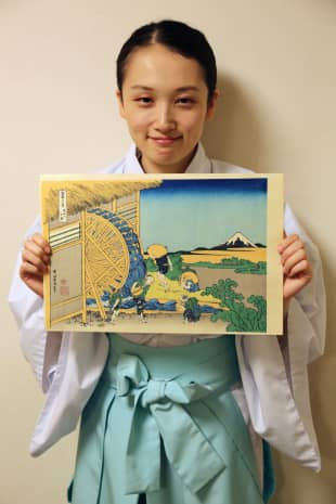 From past to present: Mutsuko Funada, head priest of Onden Shrine, holds up an old woodblock print.