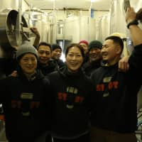 All in the family: Kaori Oshita (center) with her sister, Mayuko (left), celebrate with Minoh Beer staff. | COURTESY OF MINOH BEER