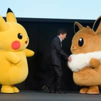 Right: Pokemon Co. CEO Tsunekazu Ishihara appears on stage with 'Pokemon' characters Pikachu (left) and Eevee during a news conference in which the company unveiled the video games 'Pokemon: Let's Go, Pikachu' and 'Pokemon: Let's Go, Eevee' in Tokyo in May. The Nintendo Switch games were released on Nov. 16 | BLOOMBERG