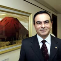 Then-Nissan President and CEO Carlos Ghosn poses beside a painting of a red-colored Mount Fuji at his office in Tokyo in March 2005. | AFP-JIJI