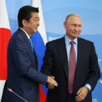 Prime Minister Shinzo Abe shakes hands with Russian President Vladimir Putin in September at the East Asian Summit, where Putin broached the idea of concluding a peace treaty by year's end 'without preconditions. | BLOOMBERG