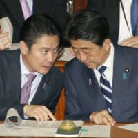 Prime Minister Shinzo Abe and Justice Minister Takashi Yamashita attend a Nov. 13 Lower House plenary session. Last week, Diet deliberations began on a bill to amend the nation's immigration law to allow more foreign workers. | KYODO