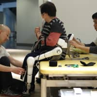 Physical therapists in Tsukuba, Ibaraki Pref., fit a robot  suit to a patient in 2014. Specific policy actions will be required to enable Japan to harness its technical strengths in the life sciences, robotics and digital innovation to better care for its rapidly aging population. | BLOOMBERG