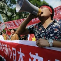 Angered by Japan's nationalization of the Senkaku Islands that month, protesters shout anti-Japan slogans near the Japanese Consulate General in Shanghai on Sept. 18, 2012 — a date that also marked the 81st anniversary of Japan's invasion of Manchuria. | AP