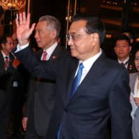 Chinese Premier Li Keqiang, shown with Singaporean Prime Minister Lee Hsien Loong on Nov. 14, signed an upgraded version of the China-Singapore free trade agreement when he visited Singapore last week. China is the largest trade partner of numerous Asian countries. | REUTERS
