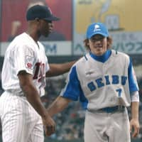 Seibu second baseman Kazuo Matsui is congratulated by Minnesota left fielder Torii Hunter after receiving the Fighting Spirit Award during the 2002 Nichibei Yakyu series at Tokyo Dome  in November. | KYODO
