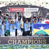 Kawasaki Frontale players celebrate the team's second consecutive J. League title on Saturday in Osaka. Frontale fell 2-1 to Cerezo Osaka, but sealed the title with three games to spare due to Sanfrecce Hiroshima's loss. | KYODO