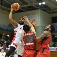 Diamond Dolphins forward Markeith Cummings shoots over two Grouses defenders in the second quarter on Friday in Toyama. | B. LEAGUE