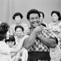 TV talk show host Akiko Kataoka admires the muscles of heavyweight champion George Foreman during an appearance in Tokyo in July 1973. | AP