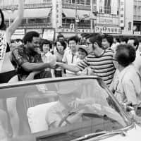 Heavyweight champion George Foreman shakes hands with a Tokyo resident during a parade through Ginza in 1973 ahead of his title bout with Jose Roman. | AP
