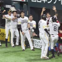 The Hawks celebrate Kenji Akashi's game-tying, seventh-inning home run against the Carp in Game 5 of the Japan Series on Thursday night at Yafuoku Dome. Fukuoka SoftBank defeated Hiroshima 5-4 in 10 innings. | KYODO